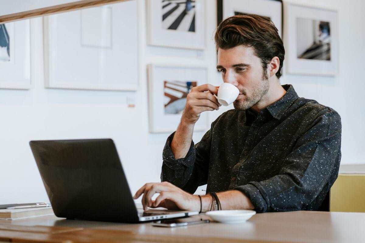 mężczyzna, pije kawę, laptop, praca