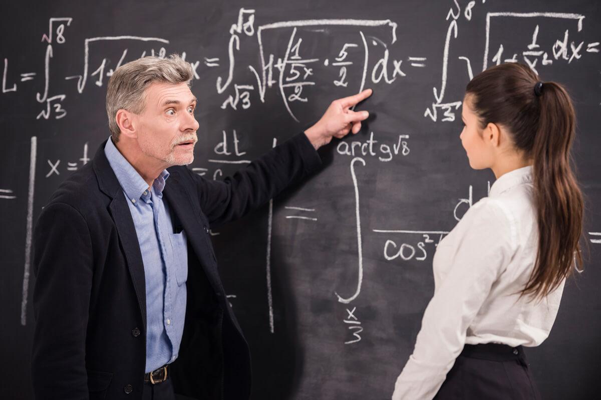 wykładowca akademicki fakty i mity nauczyciel przy tablicy tłumaczy zadanie studence matematyka wyklad szkolenie