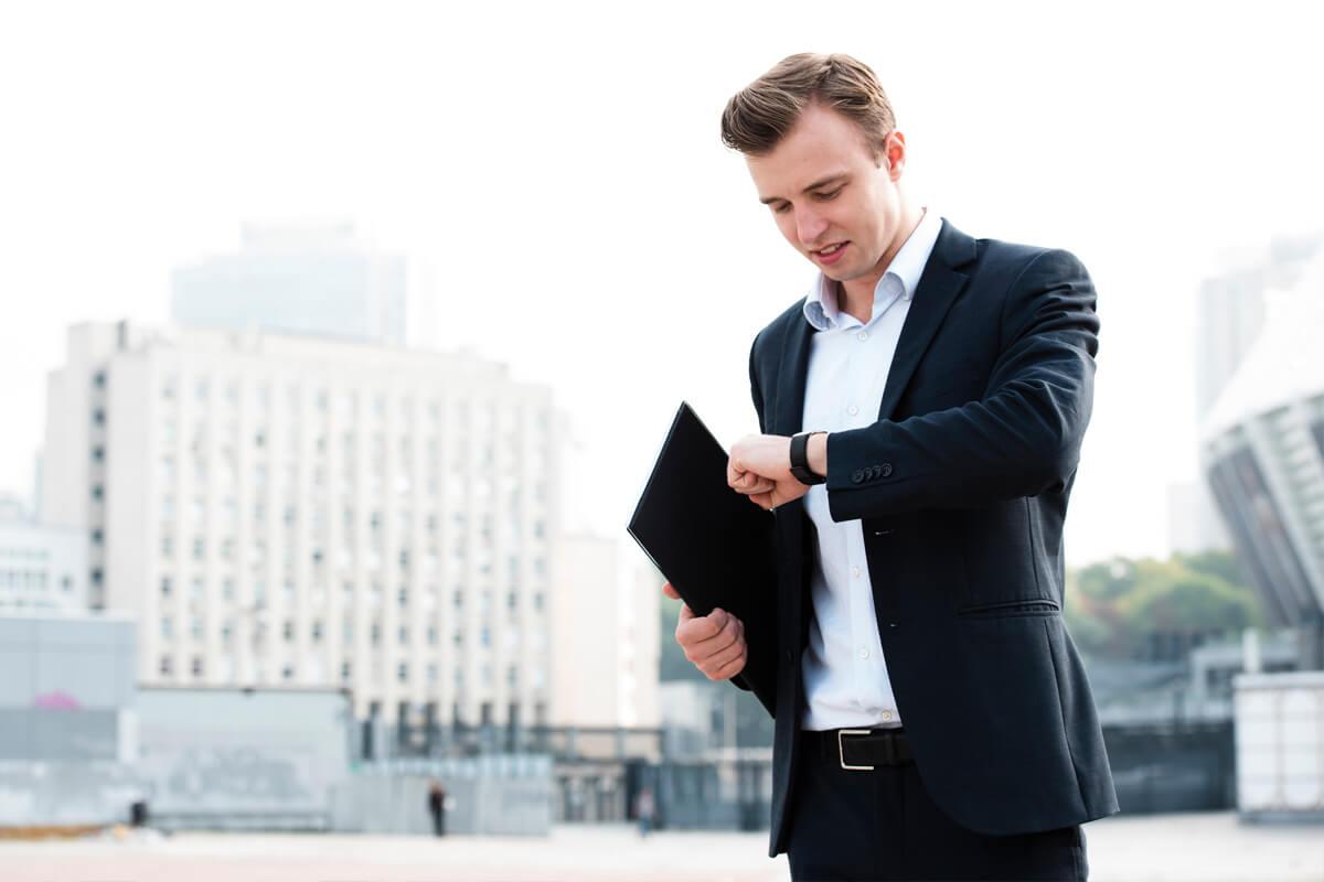 Jak mieć więcej czasu dla siebie na studiach, efektywny rozwój, szkolenia i warsztaty, Grzegorz Kobuszewski, mężczyzna patrzy na zegarek, w garniturze
