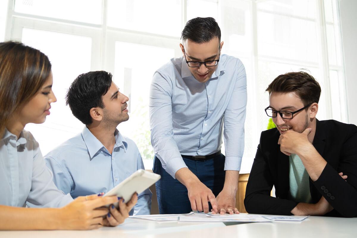 jak skutecznie pracować w grupie, praca w grupie, projekt grupowy, ćwiczenia w grupie, efektywny rozwój, szkolenia i warsztaty, Grzegorz Kobuszewski, młodzi uśmiechnięci ludzie pracują nad projektem, praca nad projektem