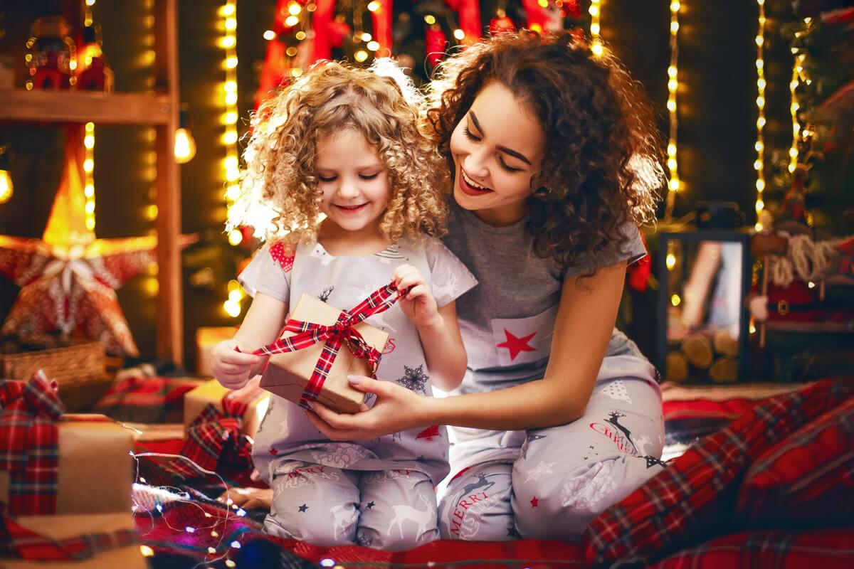 Jak efektywnie odpoczywać w święta Bożego Narodzenia? Boże Narodzenie, odpoczynek po pracy, jak odpocząć, efektywnyrozwój.pl, szkolenia i warsztaty, rozwój osobisty, kobieta z dziewczynką, rozpakowywanie prezentów, świąteczny klimat