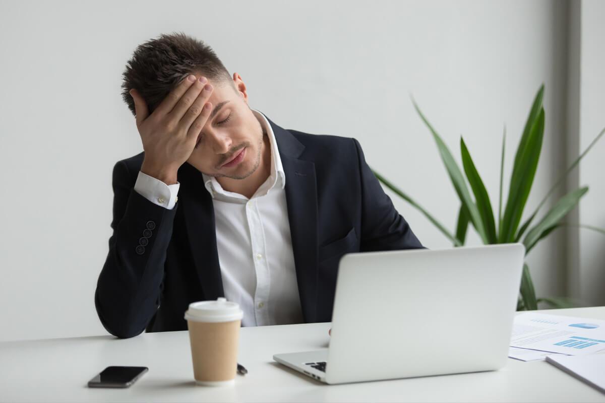 Jak efektywnie odpoczywać w święta Bożego Narodzenia? odpoczynek po pracy, jak odpocząć, efektywnyrozwój.pl, szkolenia i warsztaty, rozwój osobisty, wewnętrzna presja, za dużo biorę na siebie, mężczyzna siedzi przy biurku i martwi się