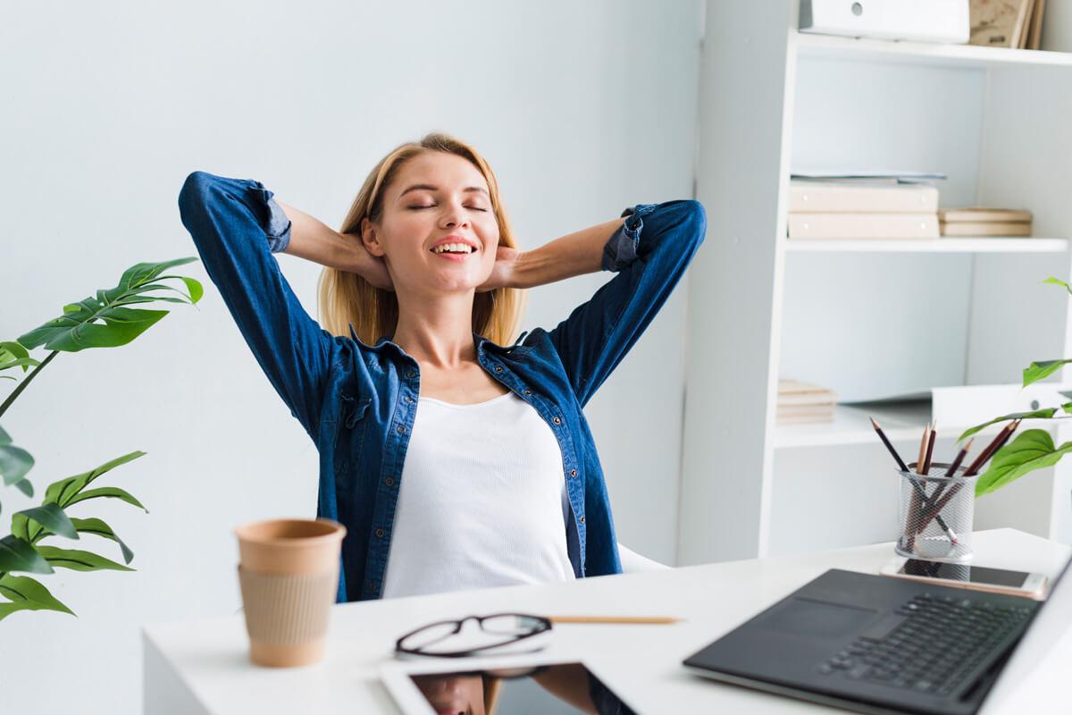 Jak efektywnie odpoczywać w święta Bożego Narodzenia? Boże Narodzenie, odpoczynek po pracy, jak odpocząć, efektywnyrozwój.pl, szkolenia i warsztaty, rozwój osobisty, kobieta siedzi przy biurku, relaks, spokój, odprężenie